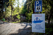 """A sign explaining to keep """"Social distance"""" in the forest and mountain bikers riding in the Taunus forest towards the mountain top """"Feldberg"""". The Taunus is a mountain range in Hessen, Germany, located north of Frankfurt."""