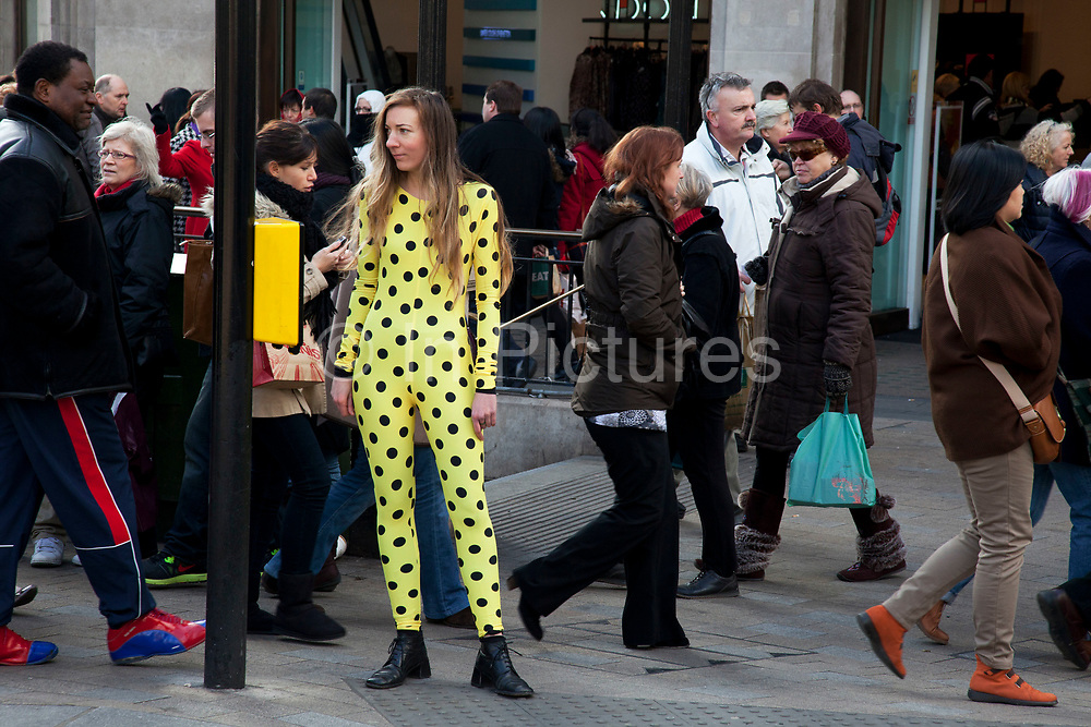 Woman dressed in a polka dot yellow morph suit waits by the side of the road in central London as passers by walk by.