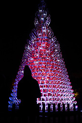 © Licensed to London News Pictures. 21/11/2017. London, UK. A visitor admires a Christmas tree made of snow sleds at the opening of Christmas at Kew at Royal Botanical Gardens, Kew. The spectacular displays are illuminated by over one million tiny twinkling lights placed all over Kew Gardens - open Wednesdays – Sundays from 22 November 2017 – 2 January 2017. London, UK. Photo credit: Peter Macdiarmid/LNP