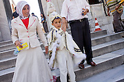 """08 AUGUST 2007 -- ISTANBUL, TURKEY: A boy in a traditional """"sünnet"""" uniform (circumcision outfit) walks with his family through a mosque in Istanbul, Turkey. Turkish boys are circumcised at between the ages of seven and nine years old. The circumcision marks the passage from boyhood to manhood. Istanbul, a city of about 14 million people, and the largest city in Turkey, straddles the Bosphorus Straits between Europe and Asia. It is one of the oldest cities in the world. It was once the center of the Eastern Roman Empire and was called Constantinople, named after the Roman Emperor Constantine. In 1453, Mehmet the Conqueror, Sultan of the Ottoman Empire, captured the city and made it the center of the Ottoman Turkish Empire until World War I. After the war, the Ottoman Empire was dissolved and modern Turkey created. The capitol was moved to Ankara but Istanbul (formerly Constantinople) has remained the largest, most diverse city in Turkey.    Photo by Jack Kurtz"""