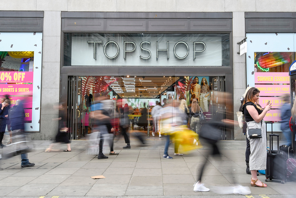 © Licensed to London News Pictures. 28/05/2019. LONDON, UK.  Shoppers pass by outside the Topshop store on Oxford Circus.  Sir Philip Green's Arcadia Group is to close the adjacent flagship Miss Selfridge store in July 2019 and move it to a concession inside Topshop.  Arcadia Group, which also includes Topshop, Wallis, Dorothy Perkins, Evans and Burton, will seek approval from creditors for a company voluntary arrangement (CVA), enabling store closures and rent cuts..  Photo credit: Stephen Chung/LNP