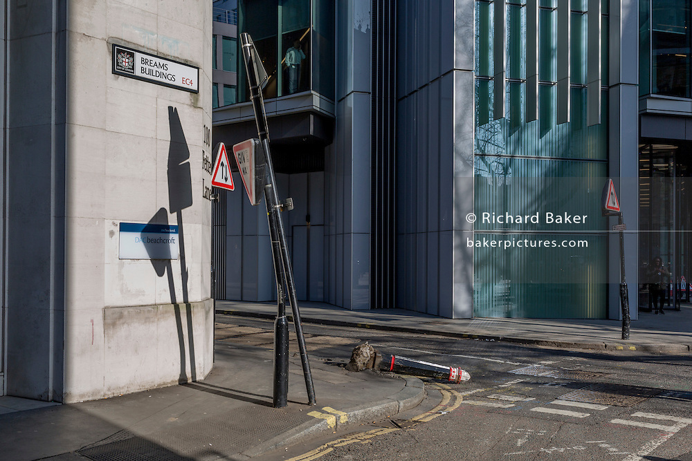 A businessman looks over the street corner where a damaged bollard lies horizontal, knocked over by a vehicle on 13th February 2017, in the City of London, United Kingdom.