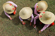 Four young Nuns cutting grass with scissors, big hats, Padonmar Sari Nunnery, Taunggyi