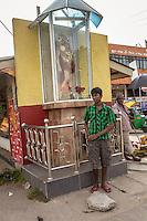 Sri Lankan adolescent stands under a Chrstian Idol