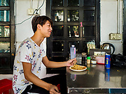 """14 FEBRUARY 2019 - SIHANOUKVILLE, CAMBODIA:  A man who works for Chinese enterprises in Sihanoukville eats lunch in a Chinese noodle shop near his apartment building. There are thousands of Chinese workers in Sihanoukville who work to support the casino and hotel industry in the town. There are about 80 Chinese casinos and resort hotels open in Sihanoukville and dozens more under construction. The casinos are changing the city, once a sleepy port on Southeast Asia's """"backpacker trail"""" into a booming city. The change is coming with a cost though. Many Cambodian residents of Sihanoukville  have lost their homes to make way for the casinos and the jobs are going to Chinese workers, brought in to build casinos and work in the casinos.      PHOTO BY JACK KURTZ"""