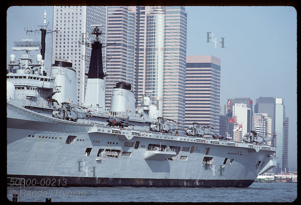 British warship eclipses row of skyscrapers in Central District on a sunny day in Hong Kong. Hong Kong