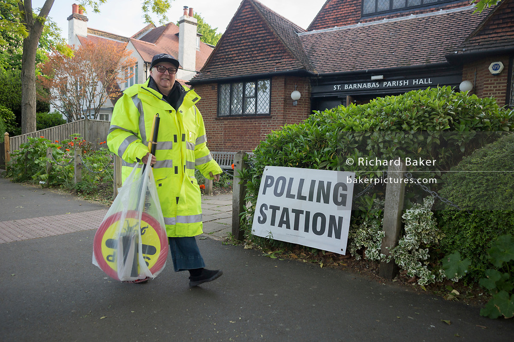 On the morning of the European Elections in the UK, a lollipop lady carries her pedestrian sign past the Polling Station at St. Barnabas Parish Hall in Dulwich Village, on 23rd May 2019, in south London, England UK.