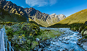 Sunset shines on peaks of the Southern Alps at the headwaters of Rees River at Shelter Rock Hut on Rees-Dart Track in Mount Aspiring National Park, Otago region, South Island of New Zealand. This image was stitched from multiple overlapping photos.