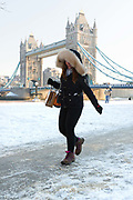 A woman wearing a fur hood walks to work on the south bank in front of Tower Bridge after snow has fallen overnight in London, England on February 28th, 2018. Freezing weather conditions dubbed the Beast from the East have brought snow and sub-zero temperatures to the UK.
