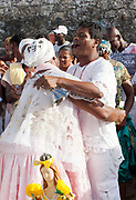 Woman being blessed by a male Babalowo Priest, Candomble group in traditional white dress taking part in a public ceremony on the beach. February 2nd is the feast of Yemanja, a Candomble Umbanda religious celebration, where thousands of adherants visit the Rio Vermehlo Red River to make offerings of flowers and prayers, paying their respects to Yemanja, the Orixa goddess of the Sea and water.