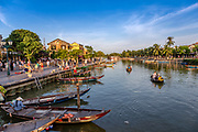 Hoi an on a late afternoon. People on the sidewalks and on the water in their wood boats.