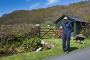 Welsh sheep farmer Howell Williams and his sheep dog Ben outside the generator room to the 15kW micro hydro power plant producing electricity at Abercrave Farm on the Brecon Beacons, Wales.