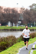 A local braves the Melbourne weather to exercise along the Yarra River during COVID-19 in Melbourne, Australia. Victoria has recorded 14 COVID related deaths including a 20 year old, marking the youngest to die from Coronavirus in Australia, and an additional 372 new cases overnight. (Photo by Dave Hewison/Speed Media)