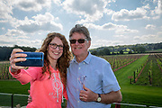 Two people smile while taking a selfie and drinking wine overlooking at vineyard at Hush Heath Winery, Staplehurst, Kent, England, UK.(photo by Andrew Aitchison / In pictures via Getty Images)