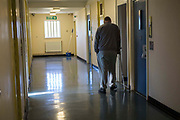 A disable prisoner walking down a corridor with crutches in Beaufort House, a skill development unit for enhanced prisoners. Part of HMP/YOI Portland, a resettlement prison with a capacity for 530 prisoners.Dorset, United Kingdom.