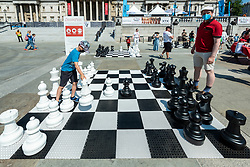 © Licensed to London News Pictures. 18/07/2021. LONDON, UK. People play chess on an outdoor chessboard at Chess Fest in Trafalgar Square.  The event celebrates the game of chess and visitors can learn the game, play chess or challenge a Grandmaster.  Also, to celebrate the 150th anniversary of Lewis Carroll's Alice Through the Looking Glass book which featured the game of the chess, 32 actors dressed as Alice Through the Looking Glass characters stand on a giant chessboard replaying a game based on the book.  Photo credit: Stephen Chung/LNP