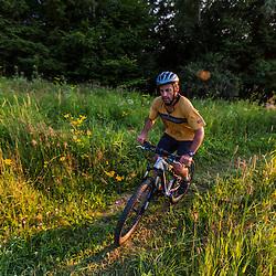 A man mountain biking in a field on Mount Ascutney in West Windsor, Vermont.