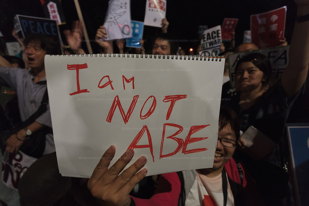 """A young Japanese protestor holds a sign that says """"I am not Abe"""" as he takes  part in a protest rally by SEALD activists outside the Japanese Diet building, Nagatacho, Tokyo, Japan. Friday July 10th 2015 SEALD (Student Emergency Action for Liberal Democracy) is a student activist group that is against the neoliberal policies and nationalist agenda of Japanese Prime Minister, Shinzo Abe."""