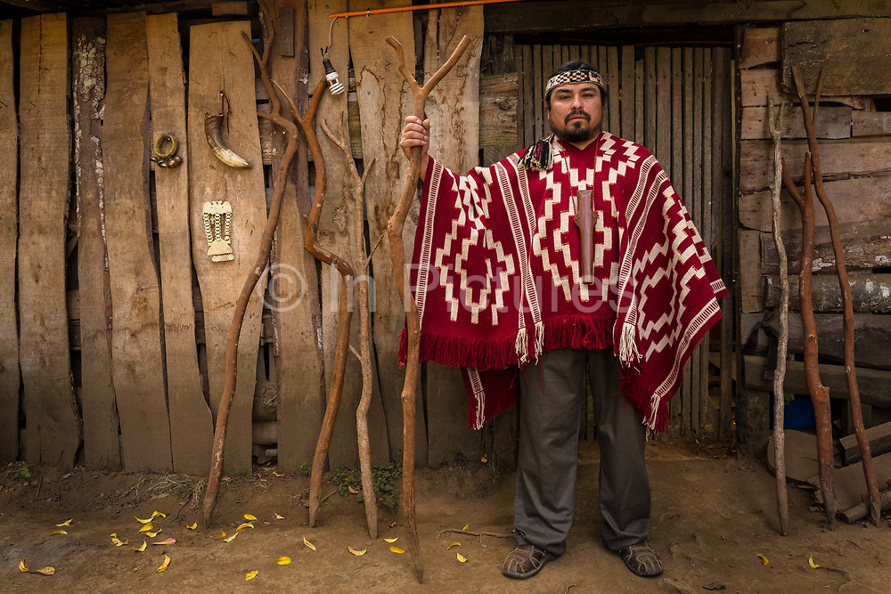 Musician and instrument maker Jose Otaiza, 43 in front of his ancestral homes entrance, 20 Kms outside Villarica town. José grew up in the poorist neighbourhood on the outskirts of Santiago. Hes a mestizo, mother being a Mapuche, father is a white Chilean. José quit schooling at an early age, to dedicate himself to music and became a street musician. He then joined a group and began touring, particularly in Argentina. He then followed his ambition and traveled across Latin America, mainly Peru, Bolivia and Ecuador to further his knowledge of Indigenous musical expressions. Following on he traveled to Europe, principally Germany  for several years before returning to reconnect with his  Mapuche  heritage which he strongly missed. Seen here with wooden stakes which in Mapuche culture have religious and mystical dimensions.  Loncoche, Chile, February 9, 2018.