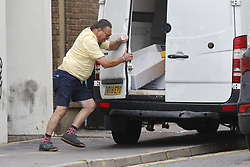© Licensed to London News Pictures. 30/07/2021. Brighton, UK. A driver struggles to close his van door in windy conditions on the sea front at Brighton, East Sussex. Parts of the south are feeling the effects of Storm Evert, the first named storm of summer 2021. Photo credit: Peter Macdiarmid/LNP