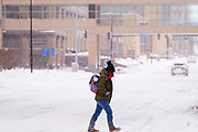26 JANUARY 2021 - DES MOINES, IOWA: A person crosses a snow packed street in downtown Des Moines. Workers in Des Moines started cleaning up a record snowfall Tuesday morning. The National Weather Service reports that 10.3 inches of snow fell at Des Moines International Airport Monday, January 25, breaking the daily record of 10 inches for January 25 set in 1895. Many downtown businesses closed for the day because of the snow, since roads throughout central Iowa were snowpacked and hard to drive.        PHOTO BY JACK KURTZ