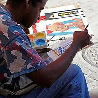 Central America, Cuba, Havana. A street artist paints a scene in old Havana.