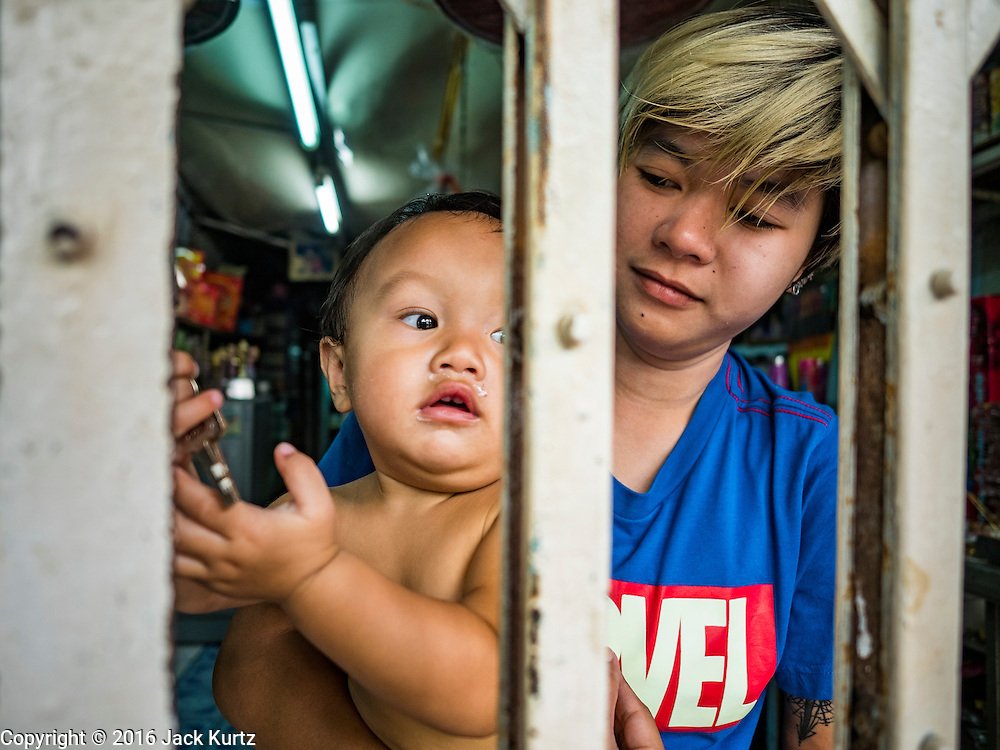 15 AUGUST 2016 - BANGKOK, THAILAND: A family in the Pom Mahakan slum waits to be served eviction notices behind the locked grill of the their home. Final eviction notices were posted today and residents of the slum have been told they must leave the fort by September 3, 2016. The Pom Mahakan community is known for fireworks, fighting cocks and bird cages. Mahakan Fort was built in 1783 during the reign of Siamese King Rama I. It was one of 14 fortresses designed to protect Bangkok from foreign invaders. Only two of the forts are still standing, the others have been torn down. A community developed in the fort when people started building houses and moving into it during the reign of King Rama V (1868-1910). The land was expropriated by Bangkok city government in 1992, but the people living in the fort refused to move. In 2004 courts ruled against the residents and said the city could take the land.      PHOTO BY JACK KURTZ
