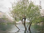 A man climbs a submerged tree in the Kachura Lake, Baltistan region.