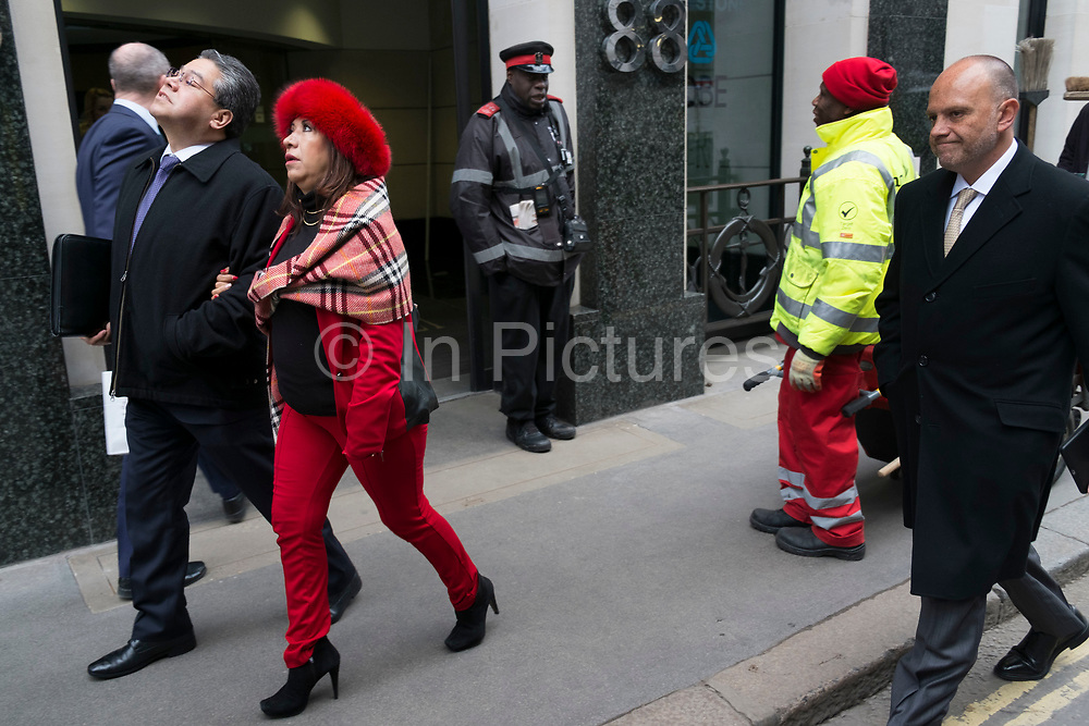 Woman wearing a red outfit and fur hat is lead by her partner through the city, arm in arm on 23rd February 2016 in London, UK. She is unaware that she is interacting and juxtaposing other red elements on the street.