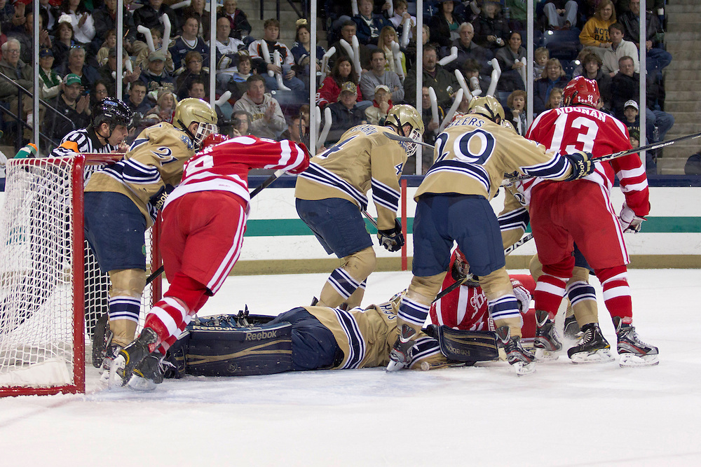 Notre Dame goaltender Steven Summerhays (#1) makes the save as players crash the net for a rebound in first period action of NCAA hockey game between Notre Dame and Boston University.  The Notre Dame Fighting Irish defeated the Boston University Terriers 5-2 in game at the Compton Family Ice Arena in South Bend, Indiana.