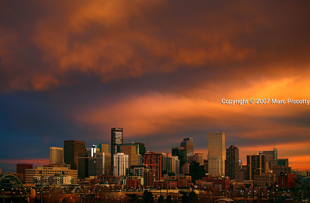 SHOT 12/3/2007 - Images of the skyline of downtown Denver, Co. at dusk as the sun sets. Denver is the capital and the most populous city of Colorado. Denver is located in the South Platte River Valley on the High Plains just east of the Front Range of the Southern Rocky Mountains. The Denver downtown district is located immediately east of the confluence of Cherry Creek with the South Platte River, approximately 15 miles east of the foothills of the Rocky Mountains. Denver is nicknamed The Mile-High City because its official elevation is exactly one mile (5,280 feet or approximately 1,609 meters) above sea level. The United States Census Bureau estimates that, in 2006, the population of the City and County of Denver was 566,974, making it the 27th most populous U.S. city..(Photo by Marc Piscotty/ © 2007)