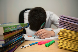 Embargoed to 0001 Friday May 04 File photo dated 05/03/17 of a school teacher looking stressed next to piles of classroom books. School leaders are suggesting that teachers should be given sabbaticals to stop them burning out and remain motivated to stay in the profession.