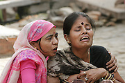 Durga Tiwari, 35, is comforted by a family member as her mother, Savitridevi Mishra, is taken to the cremation grounds of Jalasi Ghat.