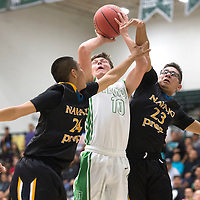 Texico Wolverine Tanner Dickerman (10) makes a shot while being guarded by Navajo Prep Eagles Isaiah Chavez (24) and Nachae Nez (23) Wednesday during the playoff game in Rio Rancho.
