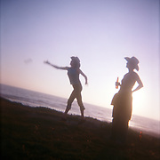 Two women tossing horseshoes in Baja California, Mexico. The ocean at sunset is in the background. Shot with Holga camera.