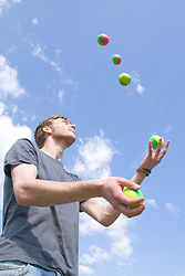 """Juggler throwing balls into the air at the Nottingham University Student Union """"Sounds on the Downs"""" Green Fields Festival; part of Green Week 2008,"""