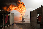 "Firefighters from the KWWK (Kuwait Wild Well Killers) attempt to kill an oil fire in the Rumaila field by guiding a ""stinger"" that will pump drilling mud into the damaged well. A ""stinger"" is a tapered pipe on the end of a long steel boom controlled by a bulldozer. Drilling mud, under high pressure, is pumped through the stinger into the well, stopping the flow of oil and gas. The Rumaila field is one of Iraq's biggest oil fields with five billion barrels in reserve. Many of the wells are 10,000 feet deep and produce huge volumes of oil and gas under tremendous pressure, which makes capping them very difficult and dangerous. Rumaila is also spelled Rumeilah.."