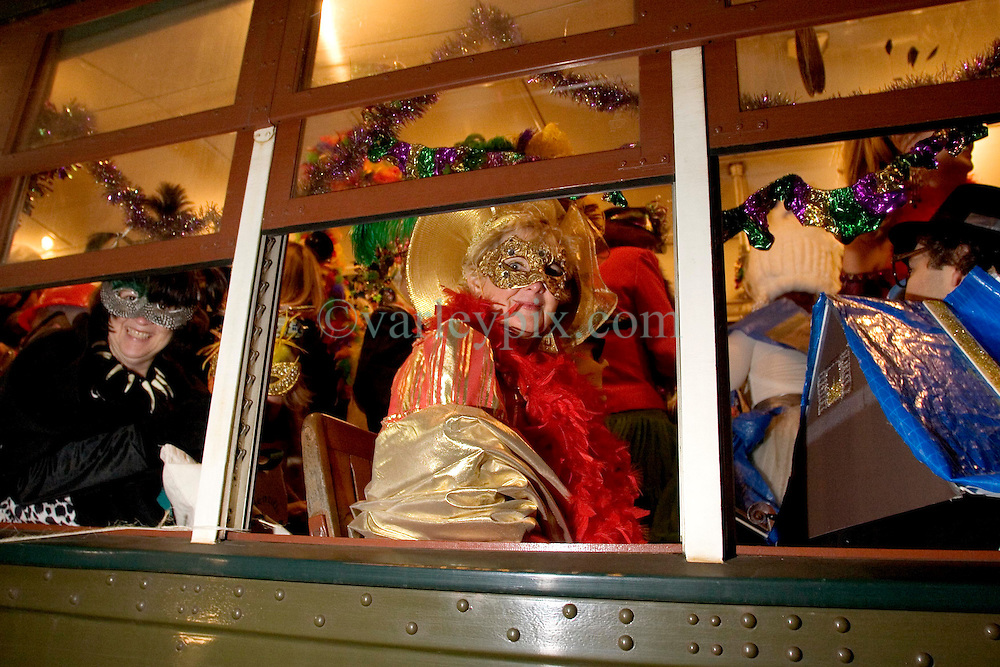 06 Jan, 2006. New Orleans, Louisiana.  Post Katrina aftermath.<br /> 12th Night, New Orleans, Louisiana. Mardi Gras begins. The Mardi Gras krewe of Phunny Phorty Phellows gather on Canal Street to take a street car through the city. Their traditional route along St Charles Ave had to be cancelled because street cars are still unable to travel the route. Diana Preston and her large hat predominate the street car.<br /> Photo; Charlie Varley/varleypix.com