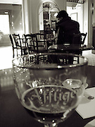 european cafe with man at table,close up of beer glass almost finnished,black and white,vertcle