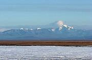 The coastal plain of the Arctic National Wildlife Refuge, with the Brooks Range in the distance, is visible across the sea ice from Barter Island in Alaska. (Steve Ringman/The Seattle Times)