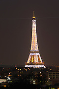 The Eiffel Tower in Paris illuminated at night against a dark blue black sky glittering special effects white blinking light making a pattern Paris France