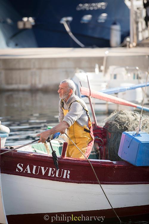 View of fisherman working in boat in harbor, Ajaccio, Corsica, France