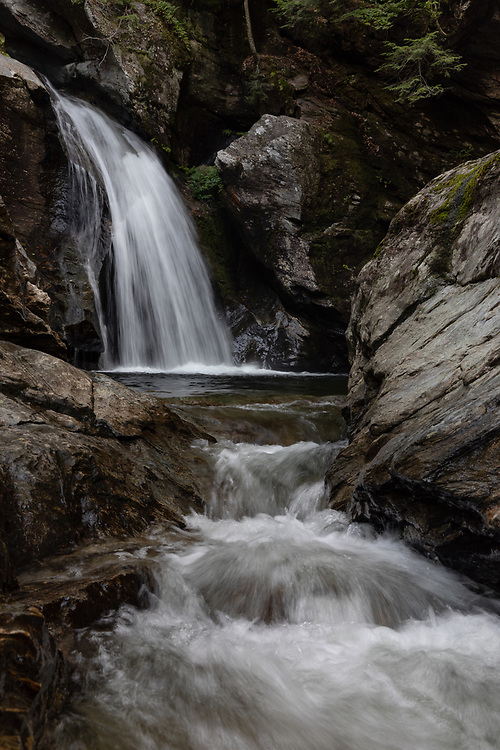 Cold mountain water rushing through Bingham Falls on a summertime afternoon in the forests of Stowe.