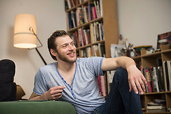 Mid adult man relaxing in living room and smiling, Munich, Bavaria, Germany