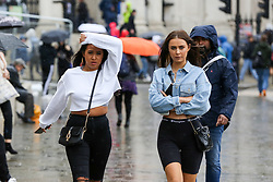 © Licensed to London News Pictures. 07/10/2019. London, UK. A woman covers her head with from the rain on a wet and windy afternoon in Trafalgar Square. Photo credit: Dinendra Haria/LNP