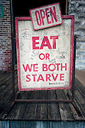 """A funny sign stating """"Eat or We Both Starve"""" outside of Taylor Grocery Catfish Restaurant in Taylor, Mississippi."""