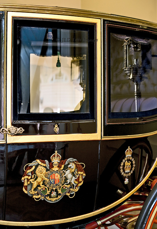 Detail of the Irish State Coach in the Buckingham Palace Mews Carriage Museum exterior showing door with royal arms, and through the windows the padded interior with tasseled window shade, and a reflection of the carriage lamp.