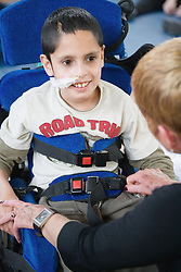 Boy with physical disability talking to his teacher,