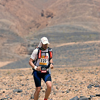 26 March 2007:  #520 Jocelyn Larabie of Canada runs across a very rocky plain during the second stage (21.7 miles) of the 22nd Marathon des Sables between Khermou and jebel El Otfal. The Marathon des Sables is a 6 days and 151 miles endurance race with food self sufficiency across the Sahara Desert in Morocco. Each participant must carry his, or her, own backpack containing food, sleeping gear and other material.
