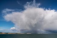 Rainbow under cumulus congestus rain storm cloud at Drakes Bay, Point Reyes National Seashore, Marin County, California